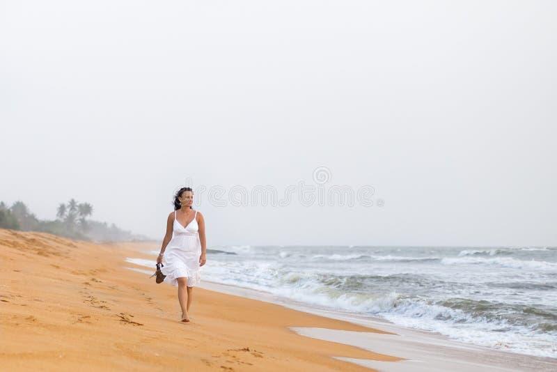 Mooie jonge vrouw die in witte kleding op het zandige strand lopen, die sandals houden Reis en de zomerconcept royalty-vrije stock foto