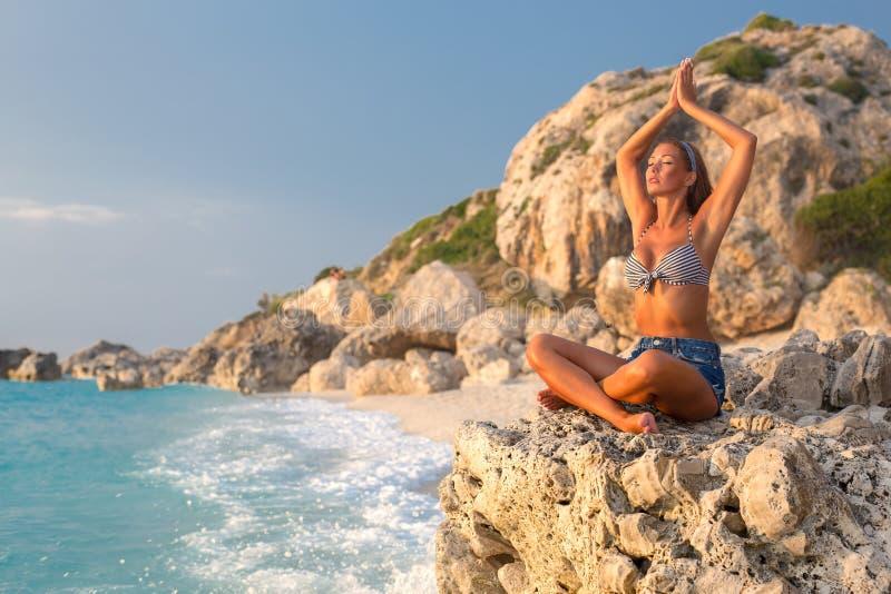 Mooie jonge vrouw die yoga op een rots doen door het strand stock afbeeldingen