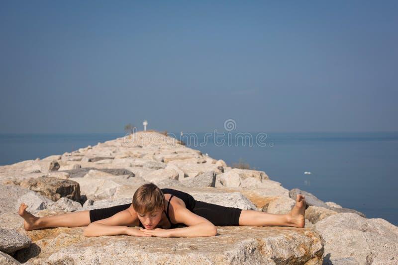 Mooie jonge vrouw die yoga op het strand doen royalty-vrije stock afbeelding