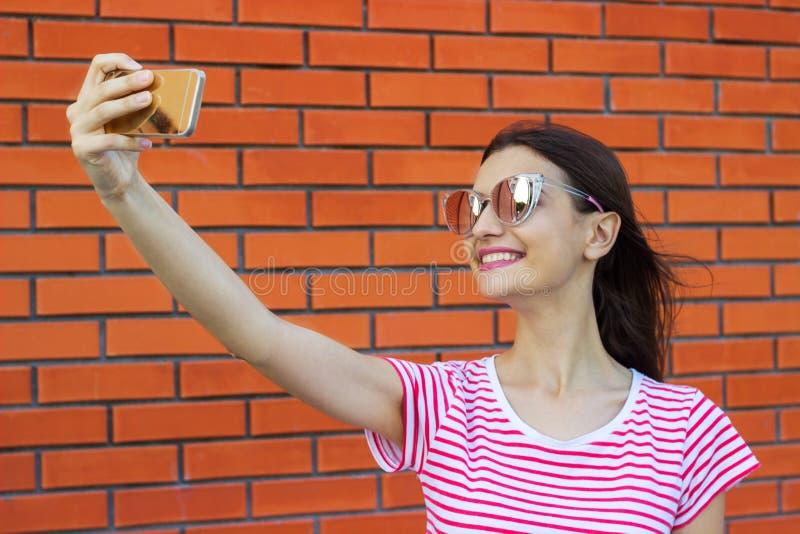 Mooie jonge vrouw die zelf-portret op een smartphone op een bakstenen muurachtergrond maken stock afbeeldingen