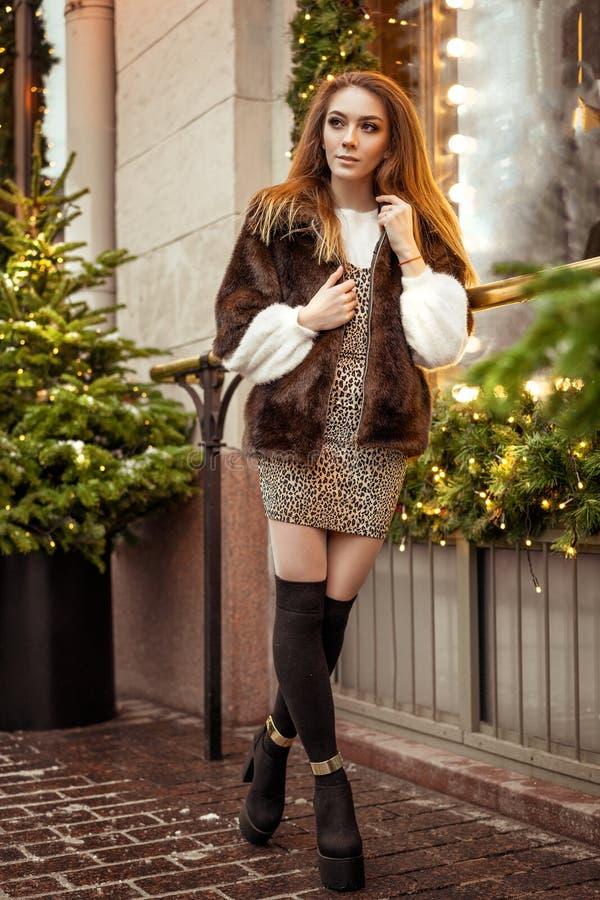 Mooie jonge vrouw die zich in de winter op de straat dichtbij het decor van venster feestelijke Kerstmis op de straten bevinden stock fotografie