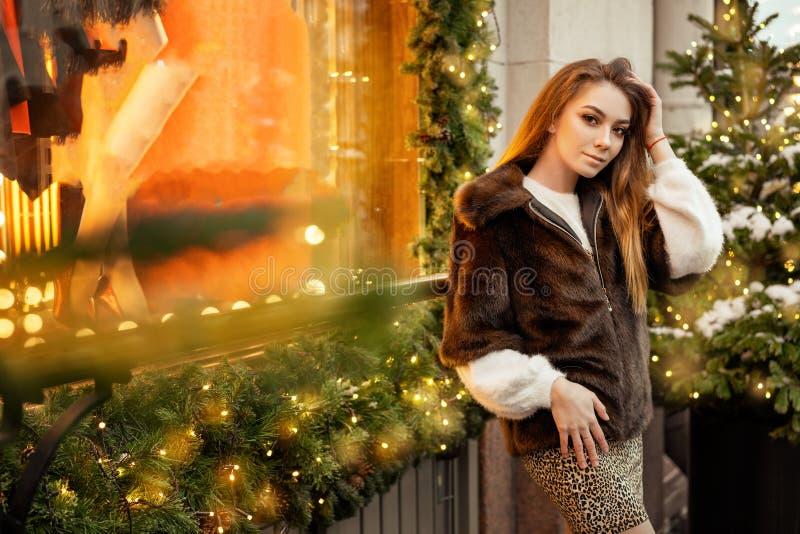 Mooie jonge vrouw die zich in de winter op de straat dichtbij het decor van venster feestelijke Kerstmis op de straten bevinden royalty-vrije stock foto
