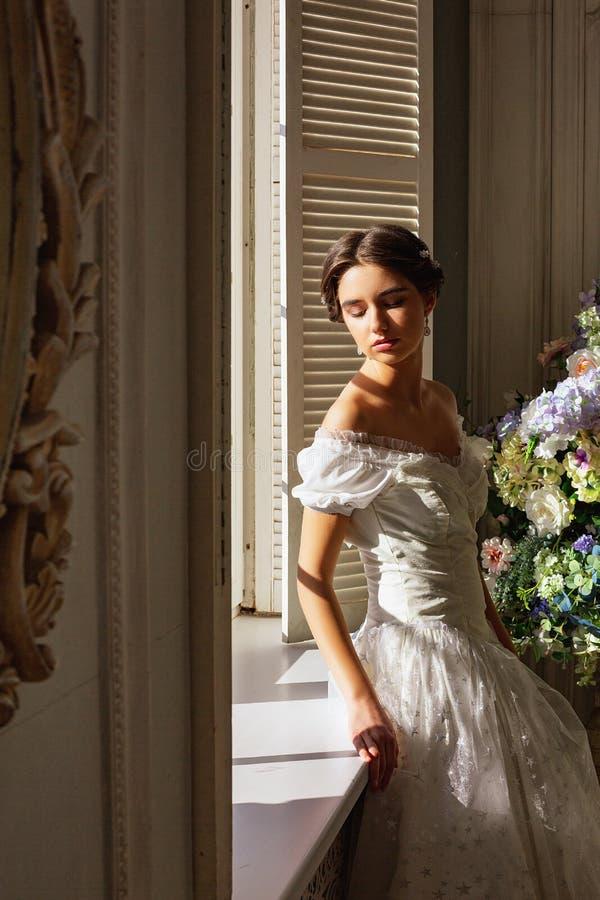 Mooie jonge vrouw die zich in witte kleding dichtbij spiegel bevinden royalty-vrije stock afbeelding