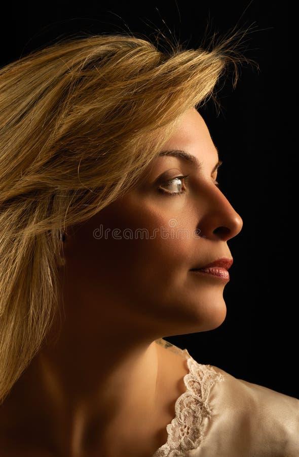 Mooie jonge vrouw die zijdelings kijkt stock foto's