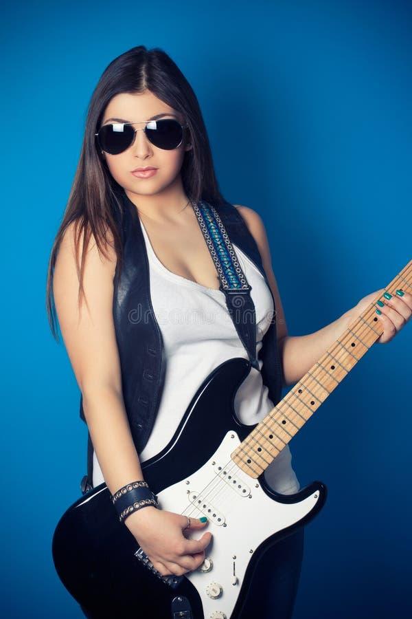 Mooie jonge vrouw die zonnebril met gitaar dragen stock afbeelding
