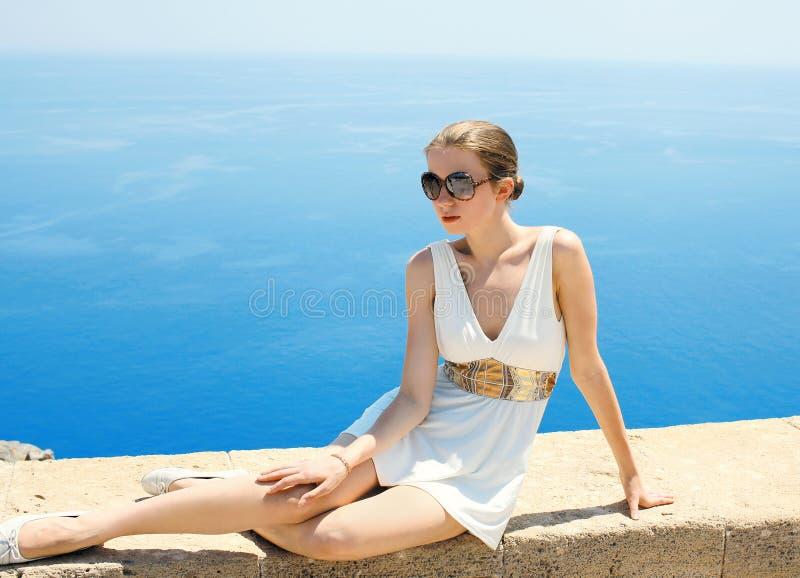 Mooie jonge vrouw in een Griekse kleding tegen het overzees royalty-vrije stock foto's