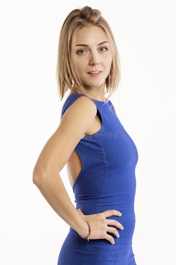 Mooie jonge vrouw in een heldere blauwe kleding die, close-up op een witte achtergrond glimlachen royalty-vrije stock afbeeldingen