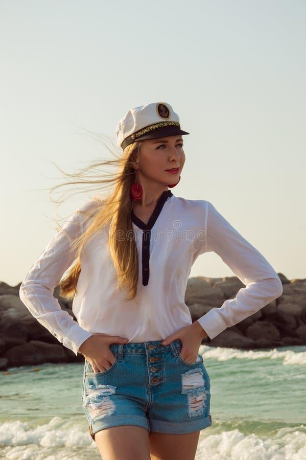 Mooie jonge vrouw in een kapiteinshoed bij het strand royalty-vrije stock afbeelding