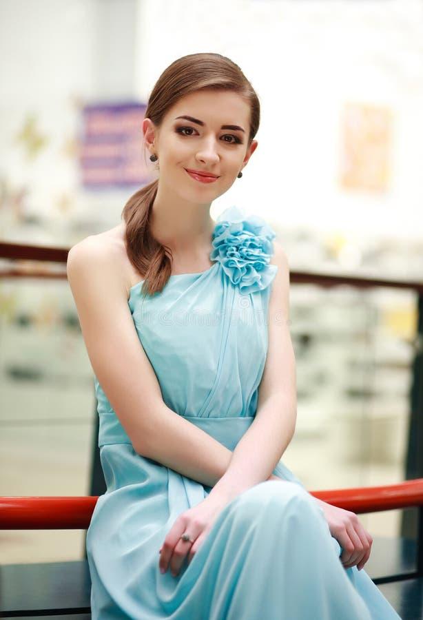 Mooie jonge vrouw in een lange blauwe kleding binnen stock fotografie