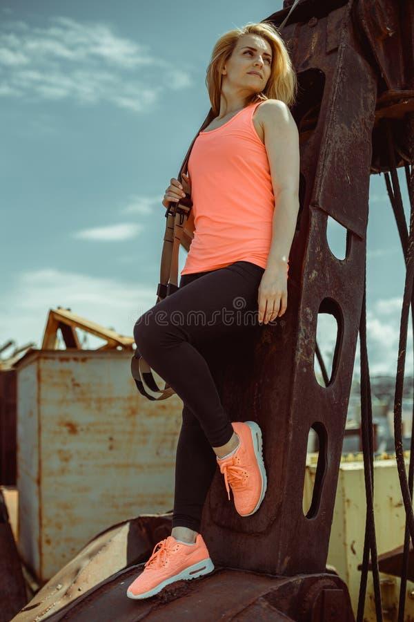 Mooie jonge vrouw in een oranje T-shirt met de riemen van de trxgeschiktheid royalty-vrije stock afbeelding