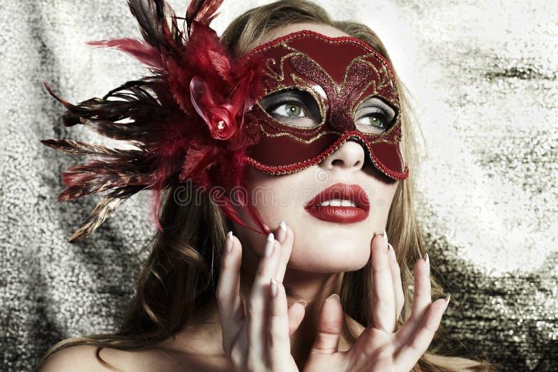Mooie jonge vrouw in een rood geheimzinnig masker stock foto's