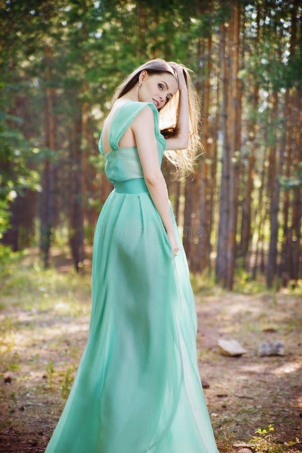 Mooie jonge vrouw in een turkooise kleding in een pijnboombos royalty-vrije stock fotografie