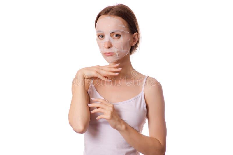 Mooie jonge vrouw een weefselmasker op haar schoonheidsmiddelen van de gezichtsschoonheid stock afbeeldingen