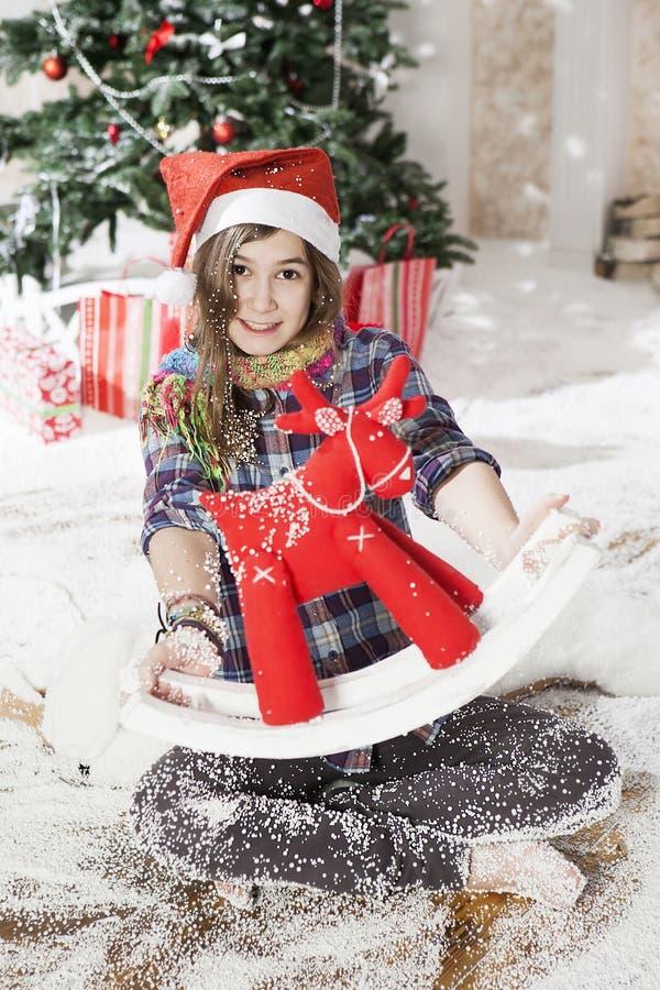 Mooie jonge vrouw in een zitting van de Kerstmanhoed op de vloer dichtbij C stock fotografie
