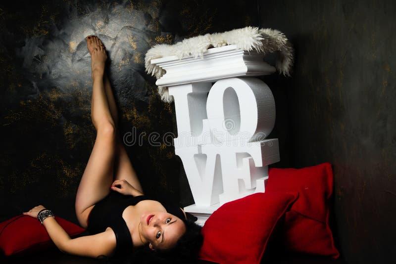 Mooie jonge vrouw in een zwarte slijtage in liefdedecoratie royalty-vrije stock fotografie