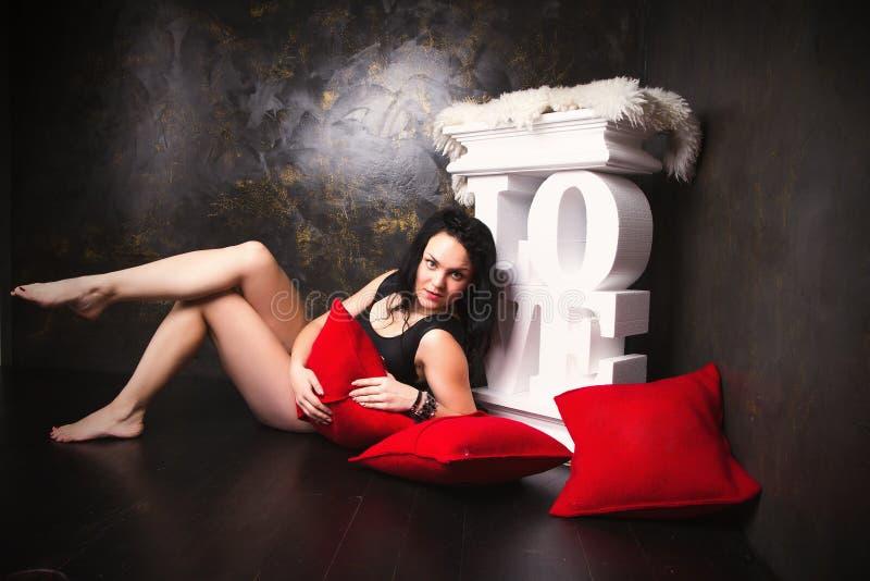 Mooie jonge vrouw in een zwarte slijtage in liefdedecoratie stock fotografie