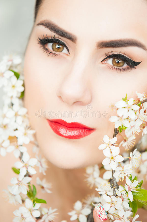 Mooie jonge vrouw en de lentebloemen royalty-vrije stock afbeelding