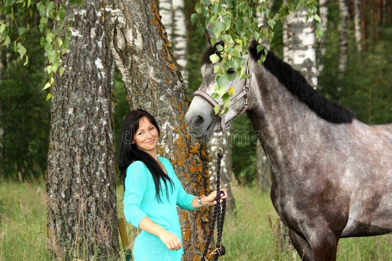 Mooie jonge vrouw en grijs paardportret stock fotografie