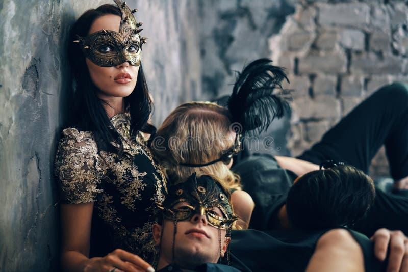 Mooie jonge vrouw en twee mannen in geheimzinnige zwarte maskerzitting op vloer in studio stock afbeeldingen