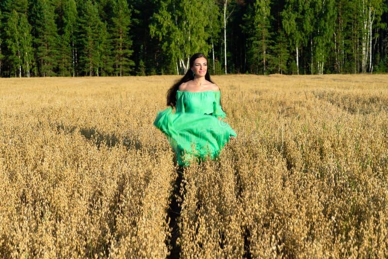 Mooie jonge vrouw in groene kledingslooppas over het tarwegebied royalty-vrije stock foto