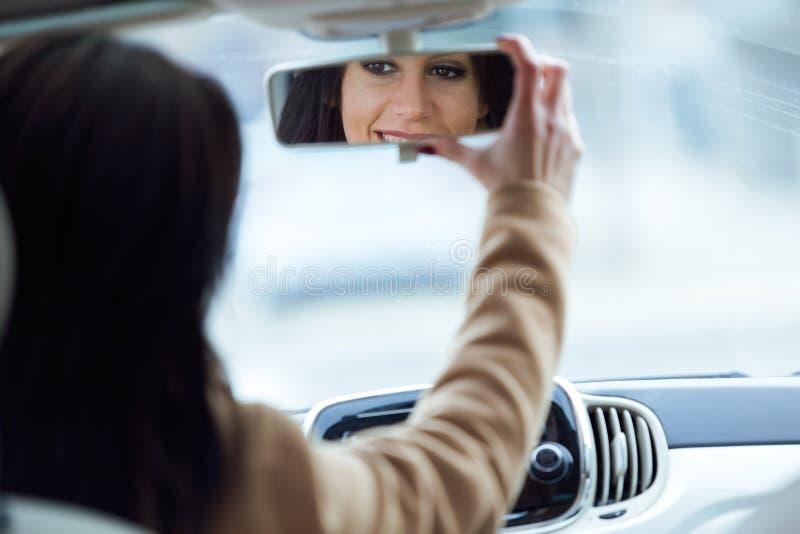 Mooie jonge vrouw het bevestigen achteruitkijkspiegel van de auto royalty-vrije stock foto