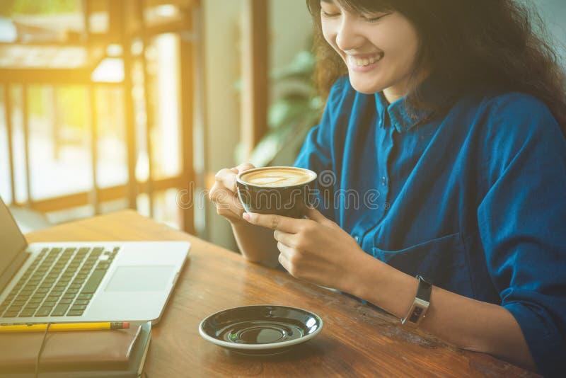 Mooie jonge vrouw het drinken koffie en glimlach stock afbeelding