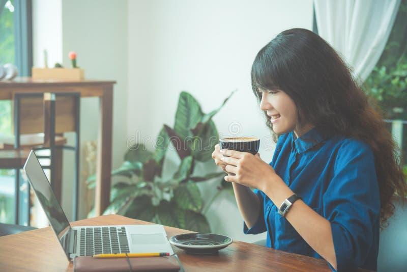 Mooie jonge vrouw het drinken koffie en glimlach stock foto's