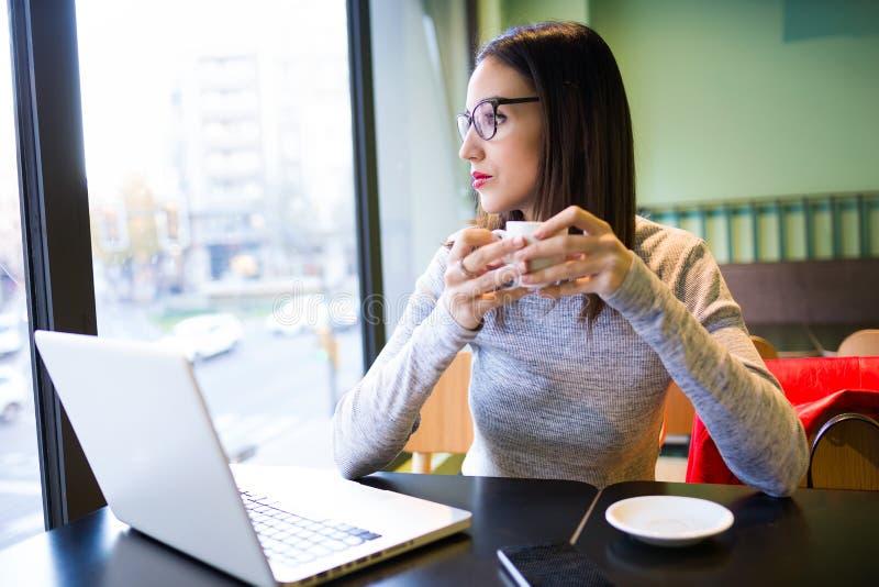 Mooie jonge vrouw het drinken koffie terwijl het gebruiken van haar laptop in de koffiewinkel royalty-vrije stock afbeeldingen