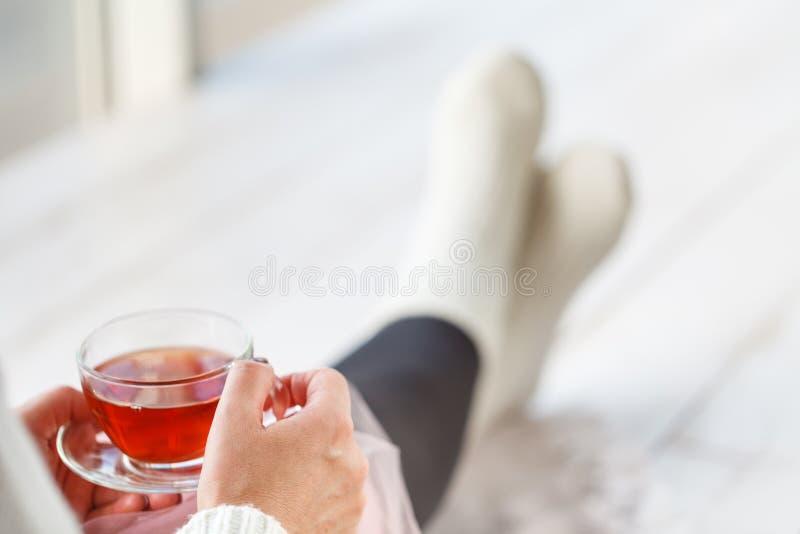 Mooie jonge vrouw het drinken thee en het kijken door venster terwijl thuis het zitten bij vensterbank royalty-vrije stock afbeelding