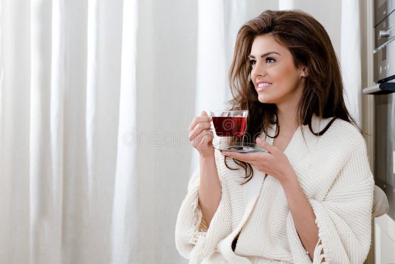 Mooie jonge vrouw het drinken thee thuis in de keuken royalty-vrije stock afbeeldingen