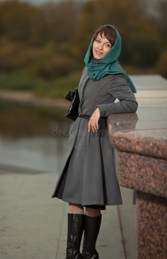Mooie jonge vrouw in het klassieke grijze laag glimlachen royalty-vrije stock foto