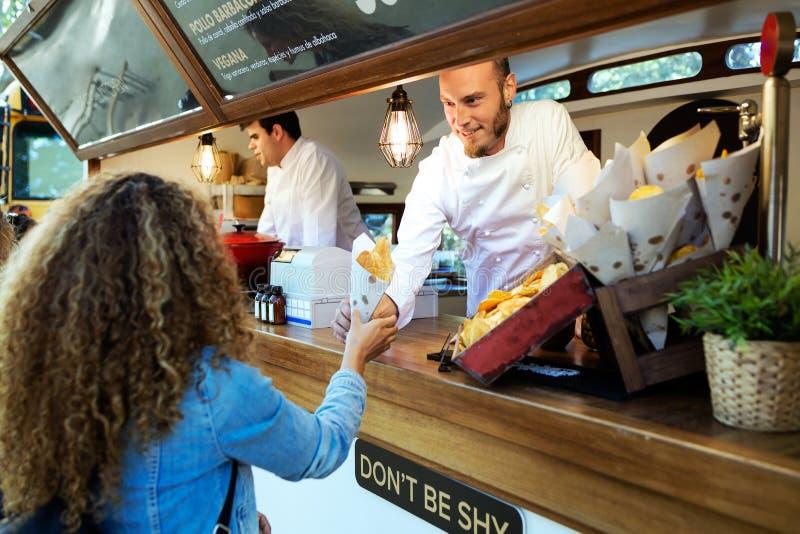 Mooie jonge vrouw het kopen barbecueaardappels op een voedselvrachtwagen royalty-vrije stock afbeelding