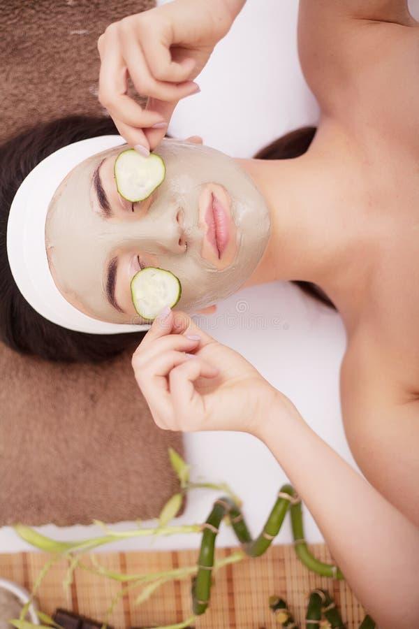 Mooie jonge Vrouw in het masker van de kleimodder op gezicht die ogen behandelen met plakkenkomkommer stock afbeeldingen