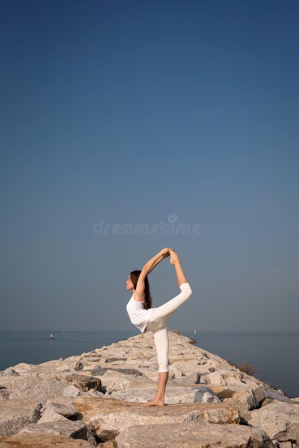 Mooie jonge vrouw het praktizeren yoga op het strand stock foto