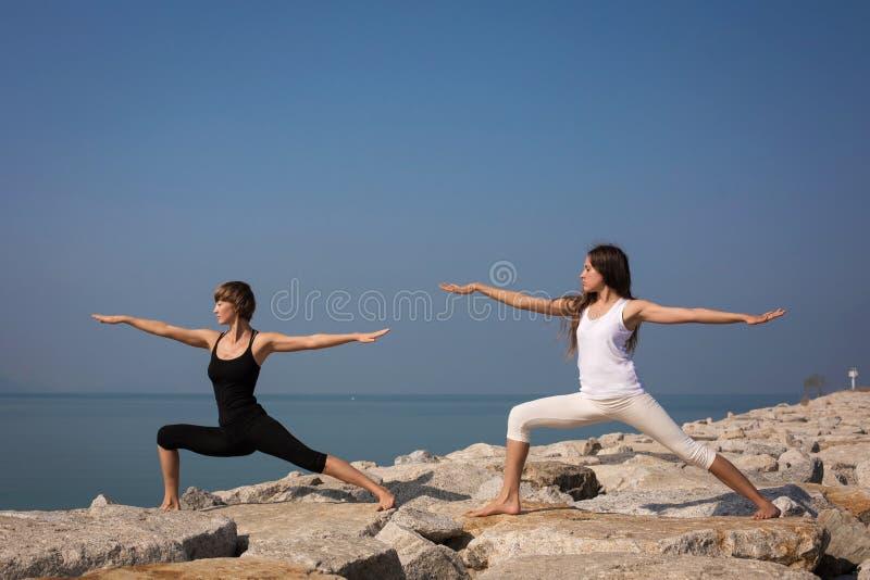 Mooie jonge vrouw het praktizeren yoga op het strand royalty-vrije stock foto's