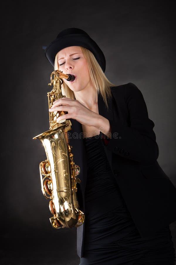 Mooie jonge vrouw het spelen saxofoon stock foto