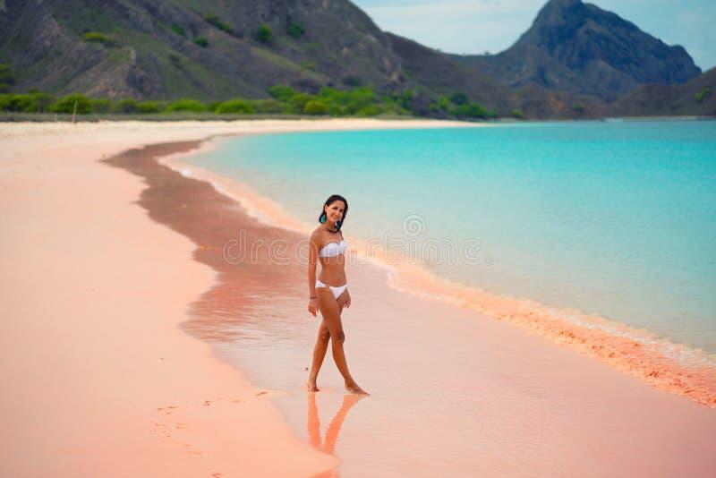 Mooie jonge vrouw in het witte bikini stellen op roze strand, eiland Lombok, Bali royalty-vrije stock afbeeldingen