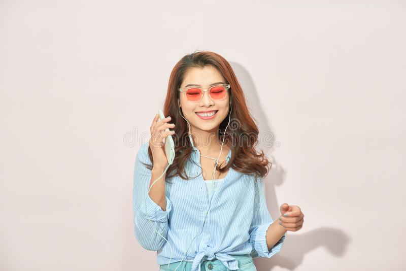 Mooie jonge vrouw in hoofdtelefoons die aan muziek luisteren en op lichte achtergrond zingen stock afbeelding