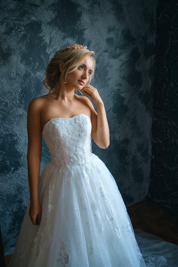 Mooie jonge vrouw in huwelijkskleding, mooie bruid met een samenstelling en kapsel stock foto's