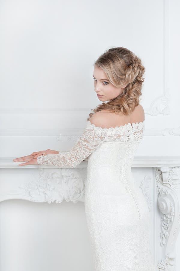 Mooie jonge vrouw in huwelijkskleding die zich in Bruids salon bevinden royalty-vrije stock fotografie