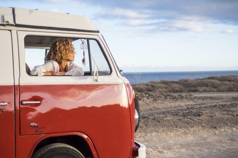 Mooie jonge vrouw Kaukasisch in vrije tijdsactiviteit met een oude bestelwagen in vakantie stock foto