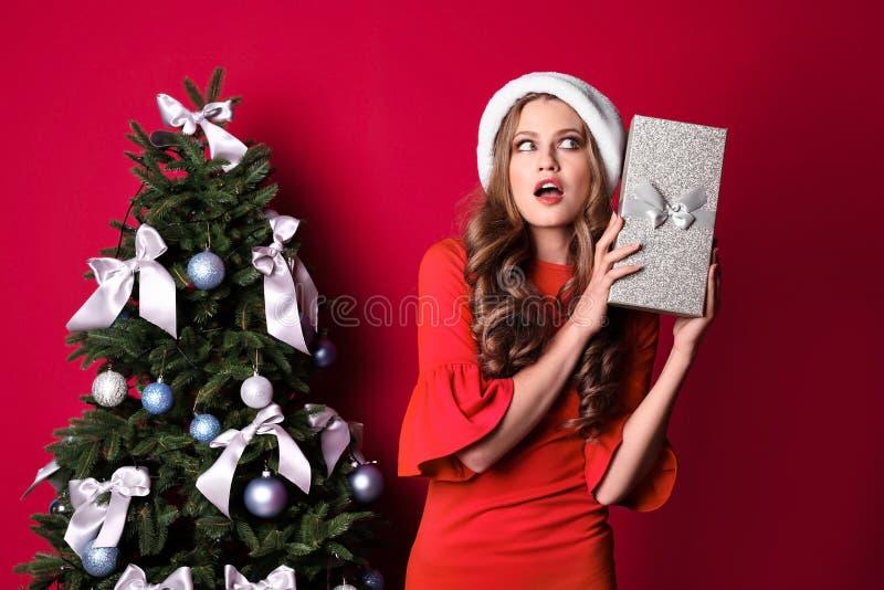 Mooie jonge vrouw in Kerstmanhoed met giftdoos dichtbij Kerstboom royalty-vrije stock foto's