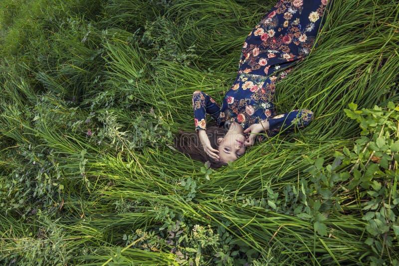 Mooie jonge vrouw in kleding die in het gras liggen stock fotografie