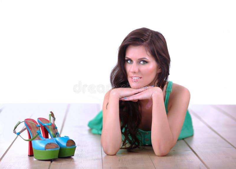 Mooie jonge vrouw in kleding die op de vloer liggen royalty-vrije stock afbeelding