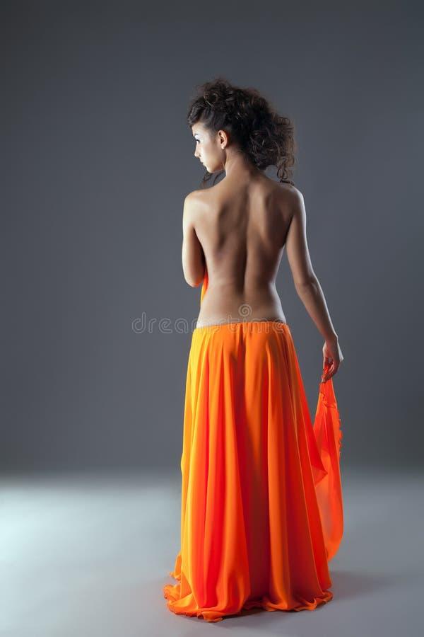 Mooie jonge vrouw in lange oranje rok stock afbeeldingen