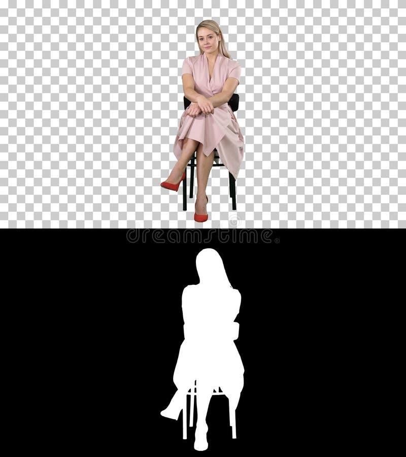 Mooie jonge vrouw, meisje, modelblonde met lange haarzitting op een stoel en het kijken aan camera, Alpha Channel stock afbeeldingen