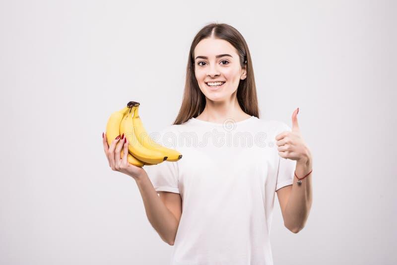 Mooie jonge vrouw met bananen op witte achtergrond, Gezondheidsconcept stock afbeeldingen