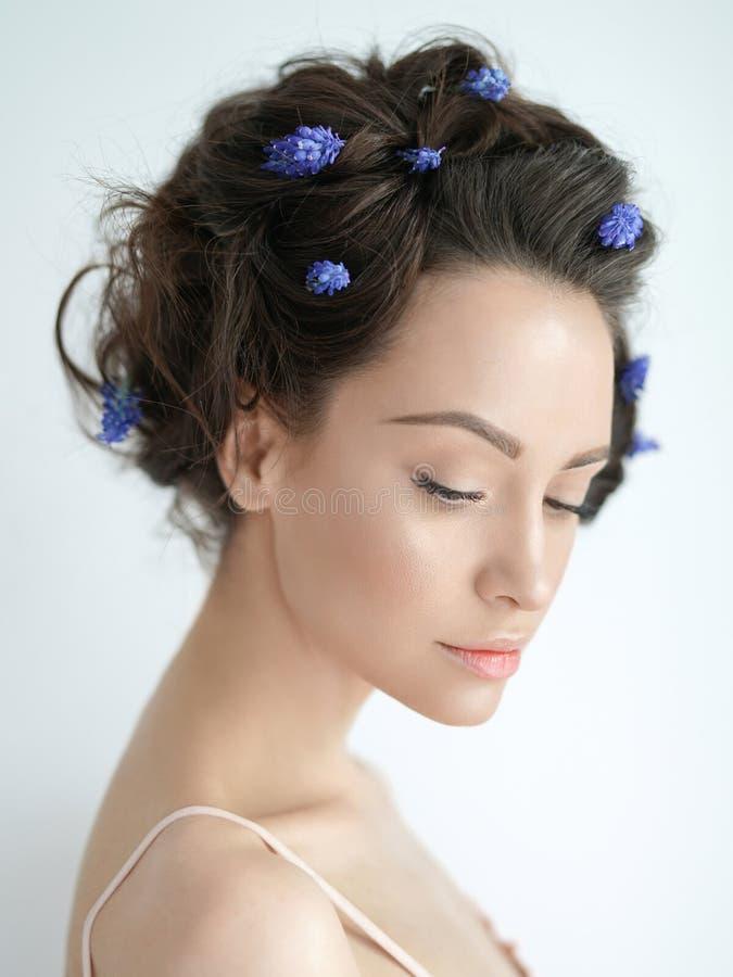 Mooie jonge vrouw met blauwe muscari in haar haar royalty-vrije stock afbeeldingen