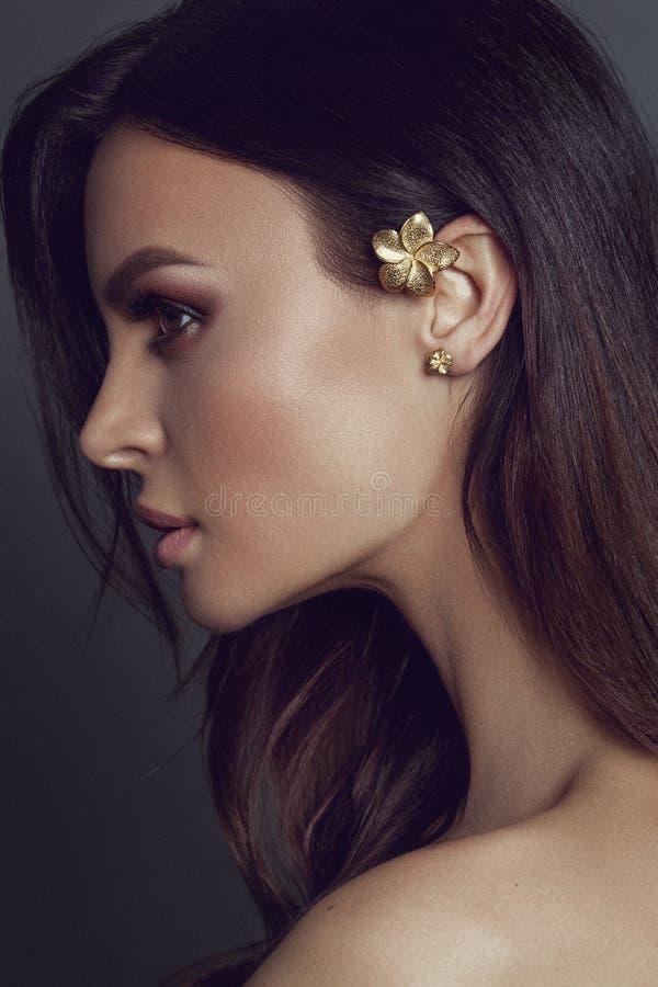 Mooie jonge vrouw met bloemkaffa in het oor Maak omhoog en Juwelenconcept - Beeld royalty-vrije stock foto