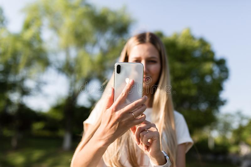 Mooie jonge vrouw met blondehaar die mobiele telefoon met behulp van openlucht Modieus meisje die selfie maken royalty-vrije stock afbeeldingen